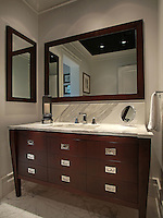 His master bath evokes a yachting theme through in the sleek dark woods and polished chrome hardware