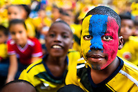 A Colombian boy, with his face painted in national flag colors, watches the football match between Colombia and Uruguay at the FIFA World Cup 2014, in a park in Cali, Colombia, 28 June 2014.