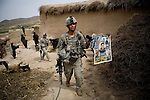 Sargeant Jeremy Johnson of the 82nd Airborne holds a Saddam Hussein poster he discovered while searching the village of Kshahah Lakhchack, Kandahar province, Afghanistan on Monday, March 26, 2007.