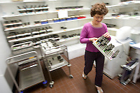A researcher collects a batch of small flies in plastic containers from the storage room at Dr. Thierry Heidmann's cancer research department at the Institut Gustave Roussy in Villejuif, France, 6 May 2008.