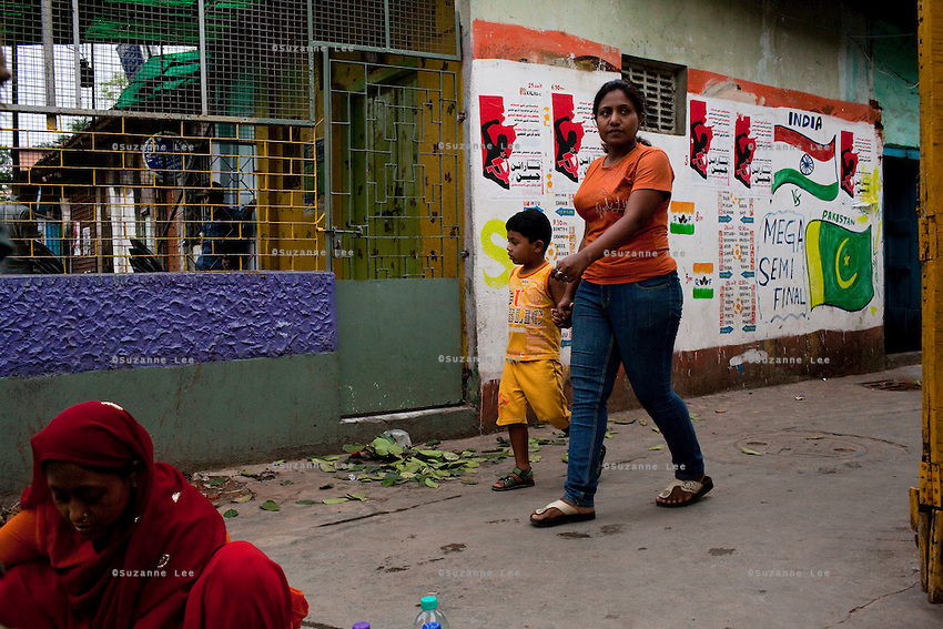 Razia Shabnam (in orange) leaves her apartment block with her son Saihaan, in Kidderpore, Calcutta, West Bengal, India as she leaves to referee an all-India invitational boxing competition in the neighbouring town of Burnpur. Razia Shabnam, 28, was one of the first women boxers in Kolkata. She was also the first woman in her community to go to college. She is now a coach and one of only three international female boxing referees in India. Photo by Suzanne Lee for Panos London