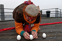 Urban shaman Donna Henes stands an egg on end during a snow squall at the South Street Seaport in New York on Friday, March 20, 2009 to welcome spring.  At the precise moment of the spring equinox, 7:44 AM, a raw egg can be  stood on its end bringing good luck for the rest of the year.  Urban shaman Donna Henes has been organizing this event for 34 years.  (© Frances M. Roberts)
