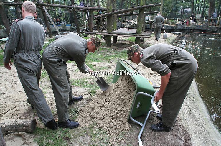 Foto: VidiPhoto..RHENEN - Militairen van het 101 CIS Bataljon (Charlie Compagnie) maandag aan het werk in Ouwehands Dierenpark in Rhenen. De soldaten doen ieder jaar op of rond dierendag allerlei klusjes in de Rhenense dierentuin. Maandag werd onder meer het verblijf van de mandrils voorzien van nieuw zand, werd de kinderboerderij geschilderd en kregen beren in het Berenbos brood en pannekoeken met honing. Het 101 CIS Bataljon draagt het dierenpark in Rheneneen warm hart toe omdat het logo van dit bataljon wordt gevormd door de kop van een tijger..