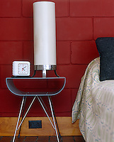 A stunning effect has been simply achieved in a bedroom by painting the brieze block walls a deep fire-engine red