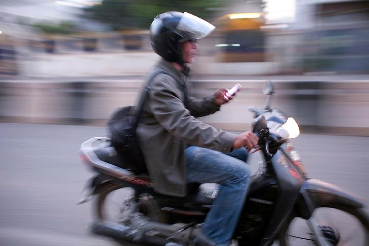 A motorcycle rider checks his smartphone in Phnom Penh, Cambodia. <br /> <br /> Photos &copy; Dennis Drenner 2013.