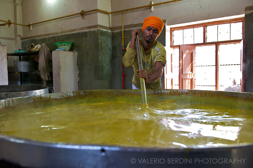 A man uses a long pole to stir a iron pot full of dal curry, the traditional Indian lentils. The pan measures at least two metres in width and one in depth, containing around 2000 litres.