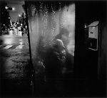 Homeless man lights a cigarette at an outdoor izakaya pub on a rainy winter night in Sanya, Tokyo, Japan.