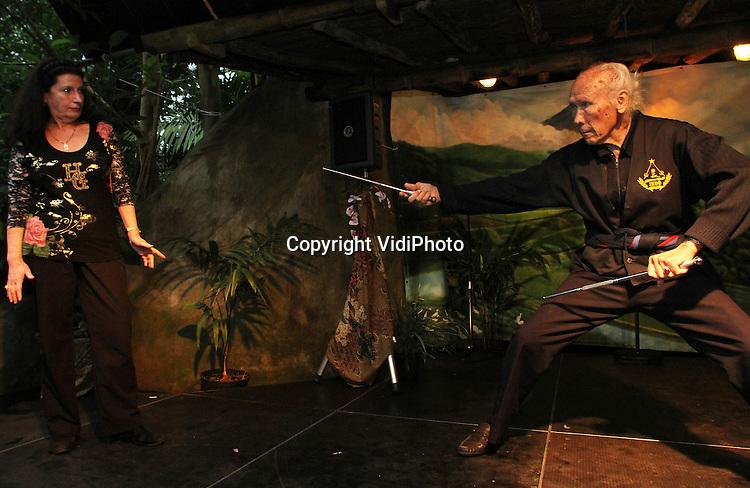 """Foto: VidiPhoto..ARNHEM - Met zang- en dansgroepen en een spectaculair optreden van de hoogbejaarde Pencak Silat-goeroe Paatje (Verdi) Phefferkorn von Offenbach (89), is dinsdag de Winter Pasar Malam van Burgers' Zoo in Arnhem geopend, ook wel bekend als """"Bali by Night"""". De Pasar Malam wordt gehouden in de overdekte regenwoud, Burgers' Bush, en duurt tot en met 7 januari. Paatje Phefferkorn is de 'schepper' van de Indo-vlag en heeft veertien Pencak Silat-scholen verspreid over heel Nederland. Pencak Silat is een Indonesche zelfverdedigingskunst. De bijna 90-jarige Paatje is de oudste 'vechtsporter' van Nederland.."""