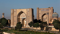 General view of Bibi-Khanym Mosque, 15th century, Samarkand, Uzbekistan, pictured on July 19, 2010, at dawn. Named after the wife of Amir Timur, 14th century ruler, the mosque was constructed following his 1399 Indian campaign. It collapsed after an earthquake in 1897 and was restored in the late 20th century. Picture shows main entrance gate (left), main building (a huge Mihrab), dome of one of three domed buildings, and 3 minarets. Samarkand, a city on the Silk Road, founded as Afrosiab in the 7th century BC, is a meeting point for the world's cultures. Its most important development was in the Timurid period, 14th to 15th centuries. Picture by Manuel Cohen.