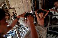 Myanmar Rohingya man is having his hair cut at a barber shop in a village of Takebi north of the town of Sittwe May 18, 2012. REUTERS/Damir Sagolj (MYANMAR)