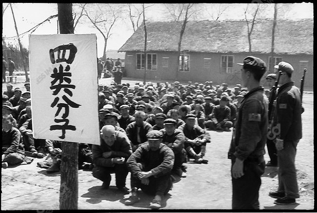 "Accused peasants are kept under guard by local militia as they wait to be denounced at a mass rally as one of the ""four elements"" - landlords, rich peasants, counterrevolutionaries, or ""bad characters"" - as indicated by the sign. Liaodian commune, Acheng county, 13 May 1965"