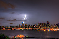 Lightning bolts illuminate the night sky over the upper west side skyline of New York City during a summer thunderstorm on Sunday, July 15, 2012.