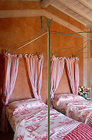 A pair of wrought-iron four-poster beds dressed in pink toile de Jouy linen with pink and white striped curtains