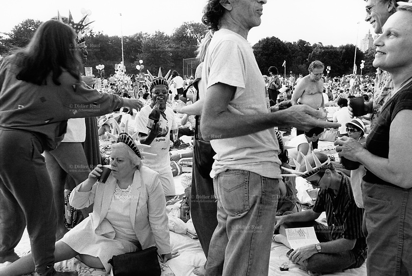 USA. New York. Central Park. An audience estimated at some 200,000 people pack the Great Lawn in Central Park to enjoy a clement summer evening, share some food and champagne, and listen to a musical concert by The New York Philharmonic with Leonard Bernstein as conductor. Four people, two men and two women, wear a plastic crown of the Statue of Liberty on their foreheads. 5.08.1986 © 1986 Didier Ruef