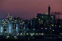 Illuminated storage tanks at a petroleum refinery at sunset, Berre, France.