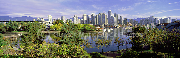 """City of Vancouver Skyline and Downtown at Yaletown and """"False Creek"""", BC, British Columbia, Canada, in Autumn / Fall.  Granville Island is in the left foreground, and the North Shore Mountains (Coast Mountains) rise above the City. - Panoramic View"""