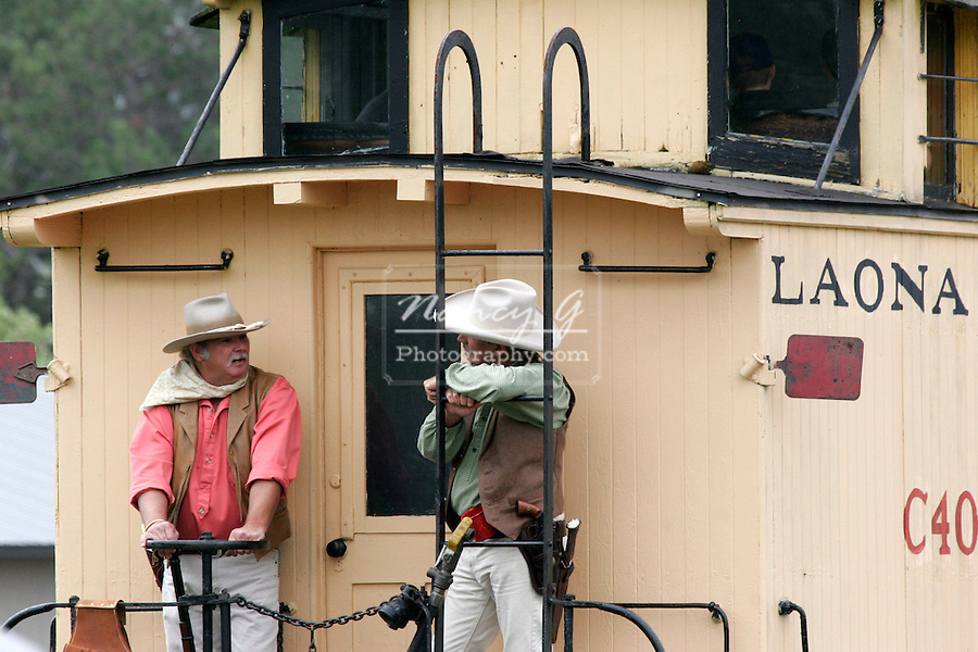 Two cowboys at the end of the train on the caboose during a 1800's western reenactment