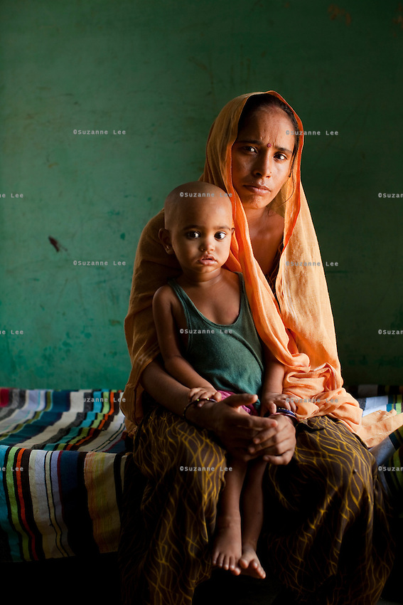 "Shashi Devi (aged 28) sits for a portrait in her house in the village of Shahpurjat, Ghaziabad, Uttar Pradesh, India. While Shashi had a tubectomy done after having 2 sons, Monika, her brother-in-law's wife, is still trying for a son after having 2 daughters. Shashi did the operation because she wanted to ""give her 2 children the best and inflation will make things difficult"", and she believes that a ""small family is a happy family"". She has been pushing Monika to get her husband to do an NSV so that Monika's life is not endangered since her previous pregnancies have been complicated. Photo by Suzanne Lee"