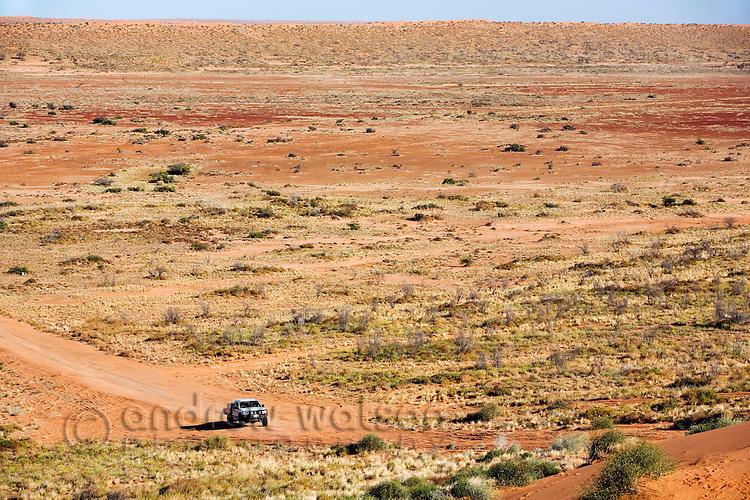A car drives through the arid landscape of the Simpson Desert National Park, near Birdsville, Queensland, Australia