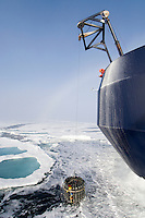 CTD (Conductivity, Temperature, Depth) device being lowered from the icebreaker research vessel into the Arctic Ocean. Water jets on the bow push ice away to maintain open water through which to dangle the CTD into the depths 2.5 miles below where a hydrothermal vent is located. Note the fogbow arched in the distance.