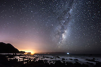 2.38am and the Milky Way rises high above Wellington's South Coast in New Zealand. The single bright light on the horizon under the Milky Way is the Baring Head Lighthouse. The glow of Wellington and the coastal suburbs of Owhiro Bay and Island Bay can be seen to the left of the photo.