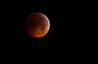 A near totally eclipsed moon rises over the Germantown section of Philadelphia in the early morning of December 21, 2010. This is the first time a total lunar eclipse has coincided with the Winter Solstice since 1638. It will not occur again until 2094.