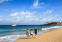 Women walk toward Black Rock at Ka'anapali Beach, Maui.