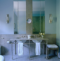 A pair of mirrors flanked by wall lights is mounted above this marble-topped double washstand