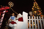 A child sits on santa's lap during a tree lighting ceremony Dec. 7 at Rancho Shopping Center in Los Altos.