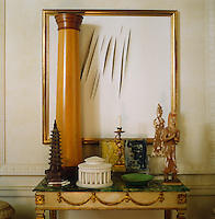 Detail of a collection of architectural models and sculpture on a marble-topped table