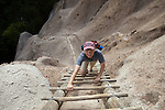 A visitor to Bandelier National Monument in New Mexico climbs a wooden ladder to reach an Anasazi cliff dwelling.