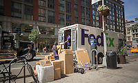FedEx workers in Midtown in New York sort packages for delivery on Saturday, July 16, 2016. (©Richard B. Levine)