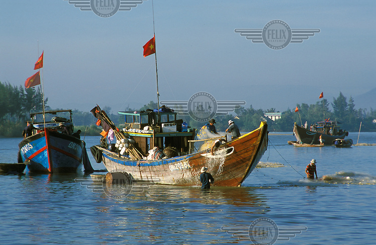 Fishermen maintaining their boats in Hoi An.