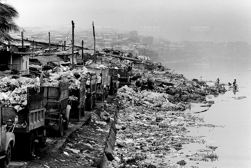 Philippines. Luzon Region. Manila. Tondo area. Smokey mountain is a rubbish dump. Life on a garbage heap. Trucks wait on line to unload their waste. A group of people wash in the river collected plastic garbage in order to resell them for a better price as recycled products. A boy climbs on a truck. © 1992 Didier Ruef ..
