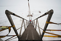 Researchers get to the ice by walking down this very steep ramp. It's not resting on the ice; it's hanging from a crane. So not only is it steep, it bounces at the bottom end. In the background are orange flags that mark the edge of the safe area of the Bering Sea ice.