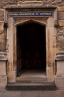A door, with Schola Grammaticae et Historiae above it in gold letters on blue, opens from the courtyard at the Bodleian Library.