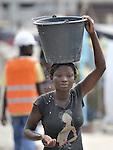 A survivor of the January 12 earthquake carries water in the Belair neighborhood of Port-au-Prince, Haiti.