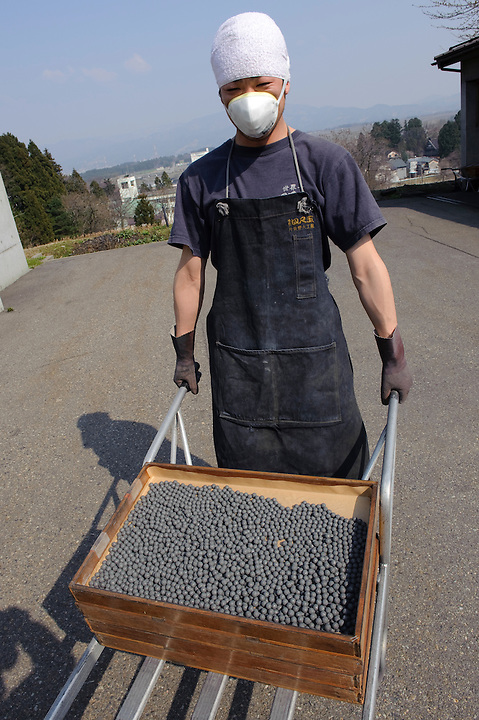 "A worker wheels a tray of gunpowder balls at Katakai Fireworks Co., Ltd, Katakai, Japan, April 6, 2009. The company makes the world's largest firework, a 120cm round shell called a ""yonshakudama""."