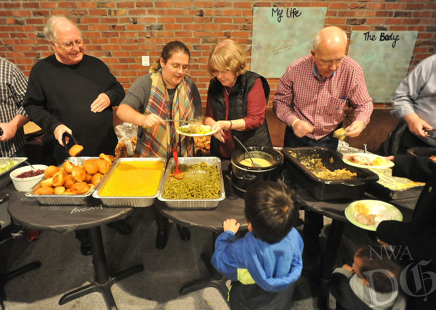 NWA Democrat-Gazette/MICHAEL WOODS &bull; @NWAMICHAELW<br /> Gene Bursey (from left), Aimee Meyer, Carol Bursey, and John Meyer  serve up a free meal Tuesday, November 17, 2015 during the  34th annual Thanksgiving dinner for UA students at the Rock House in Fayetteville.  The event hosted by Christ on Campus, a non-denominational ministry on the UA campus, feeds around 300 university students.  It is a cooperative effort with Christ on Campus and several local churches including Community Christian Church in Fayetteville and Rogers Christian Church.