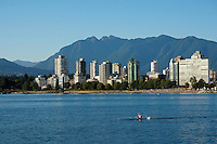 Kayaker on English Bay with West End skyline and North Shore mountains in background, Vancouver, BC, Canada