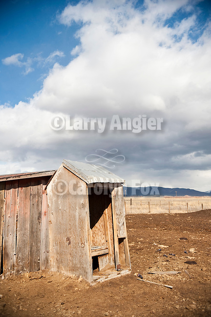 Open door outhouse and clouds at the Buckingham Ranch