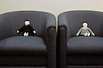 Voodoo dolls sitting in chairs in office lobby dressed as business men in a black suit and blue tie and grey suit with grey tie very formal