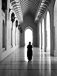Islamic figure seen in silhouette in cool building
