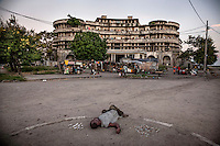 A drunk man lies on the ground in front of the former Grand Hotel building. Once a luxury destination for the wealthy and the continent's biggest hotel, the building is now a concrete shell and home to about 6,000 squatters. Those unable to occupy one of the rooms sleep in the corridors, basements and even on the roof of the building.