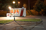 Bright lights illuminate a French ADA car rental kiosk in an empty car park alongside the N186 motorway in southern Paris.