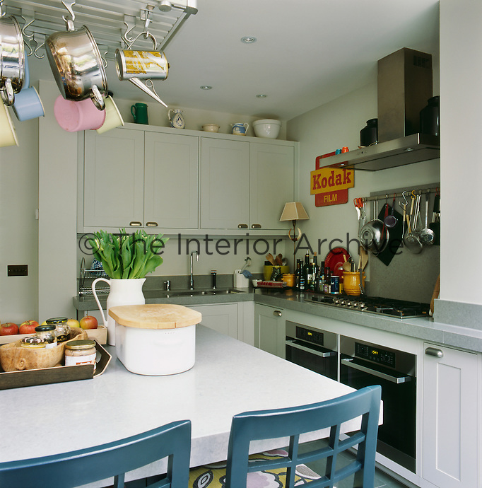The kitchen has white units and grey work surfaces. There is plenty of room for a dining table and chairs in the centre of the room