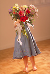 young girl hiding behind bouquet of flowers
