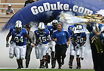30 September 2006: Duke head coach Ted Roof (3rd from left) and players Greg Meyers .(34) and Beau Tooley (45) lead the team onto the field. The Duke University Blue Devils lost 37-0 to the University of Virginia Cavaliers at Wallace Wade Stadium in Durham, North Carolina in an Atlantic Coast Conference NCAA Division I College Football game.