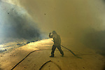 Members of the fire brigade work around the area where a fire burns in the Baixa Limia Serra do Geres Natural Park, in Lindoso north of Portugal, on August 10, 2010. (c) Pedro ARMESTRE