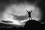 inspiring concepts, nature scenery landscapes, and travel destinations: anonymous silhouette man arms raised into cloudscape cloud sunset sky, sandia mountains, albuquerque, new mexico, usa, black and white